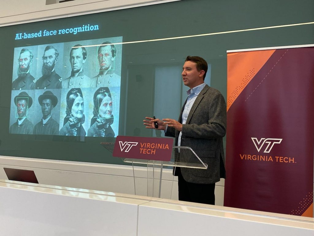 "Kurt Luther standing at a podium, speaking, and gesturing in front of a screen with the words ""AI-based face recognition"" and Civil War-era portraits"